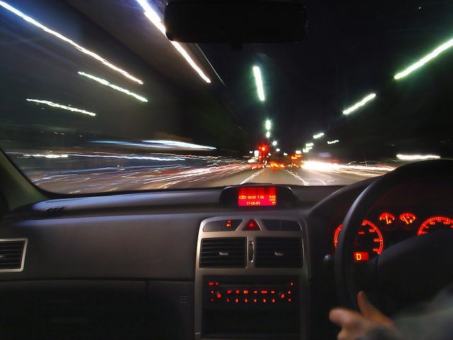 z pohledu auta je vidět rozmazaná cesta a rychlá světla, volant na pravé straně i budíky
